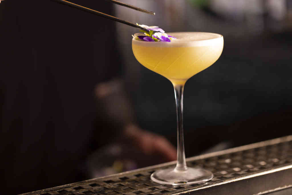 specialty cocktail with floral garnish