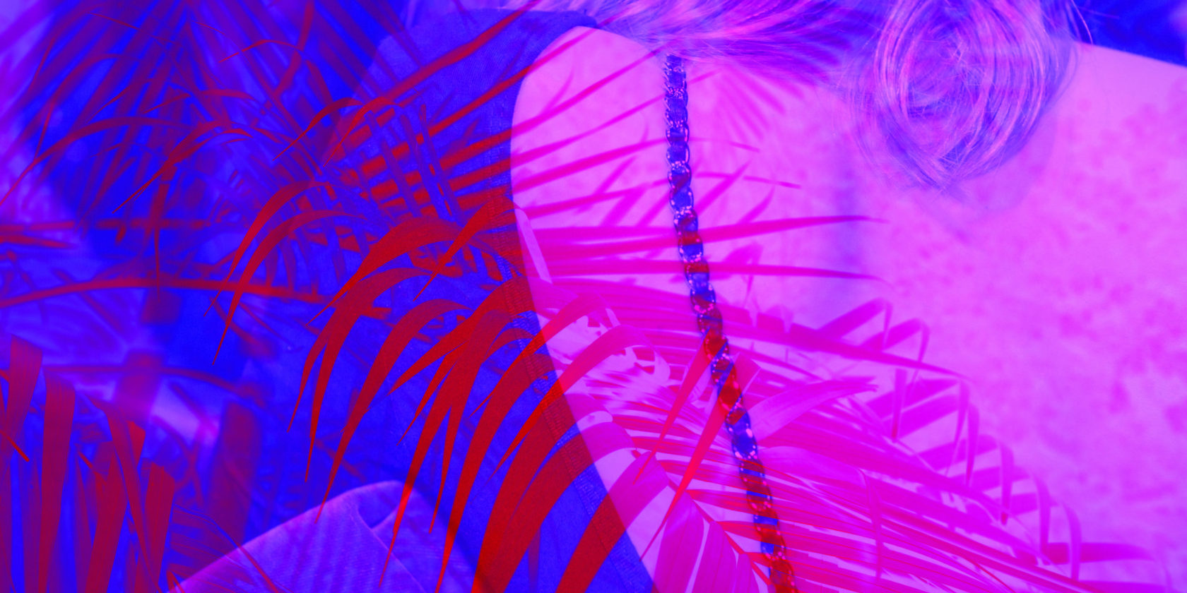 Blurred palm tree leaves and woman's back